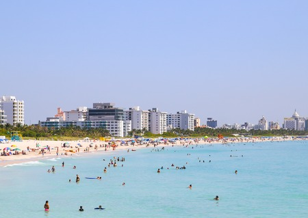 shallow water: Section of the Miami Beach with people sunbathing and swimming in the shallow water. Stock Photo