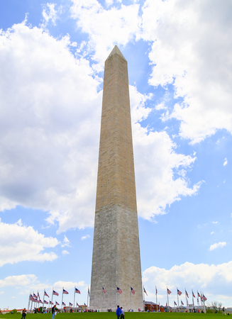 Upright format of the Washington Monument with blue sky and white clouds.