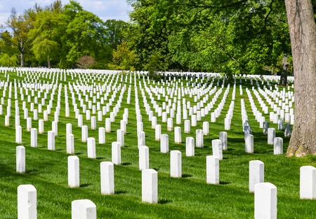 White gravestones on the green lawn of Arlington National Cemetery.