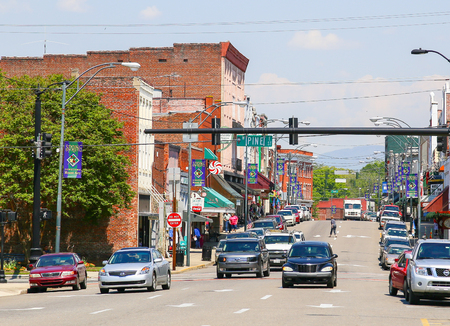 bluegrass: Mount Airy, NC, USA - May 5, 2015: Downtown Mount AIry with signs displaying Spring at the lampposts. There are some cars and pedetrians on the street and sidewalk. Editorial