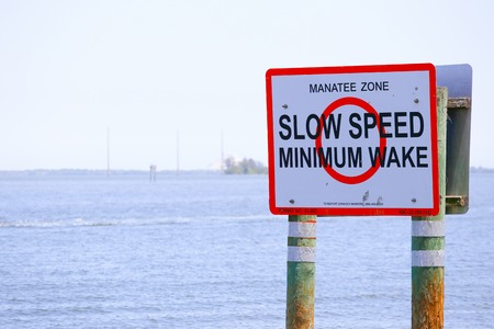 """cocoa beach: Marker in the water displaying """"Manatee Zone"""" to remind boaters of going only by slow speed and with minimum wake in order to protect the manatees."""