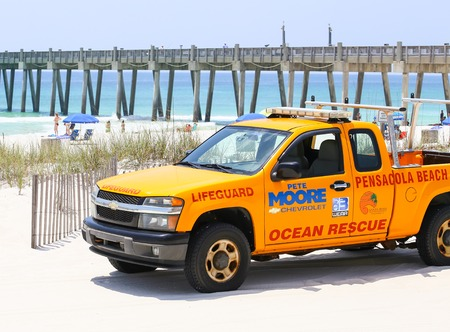 pensacola: Pensacola Beach, USA - May 13, 2015: Lifeguard pick-up truck in front of the beach and the Pensacola Beach Gulf Pier.