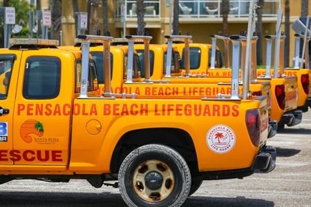 pensacola: Pensacola Beach, USA - May 13, 2015: Several lifeguard pick-up trucks parked in a row ready for use.