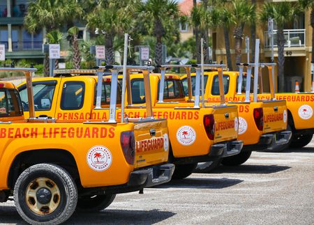 Pensacola Beach, USA - May 13, 2015: Several lifeguard pick-up trucks parked in a row ready for use.