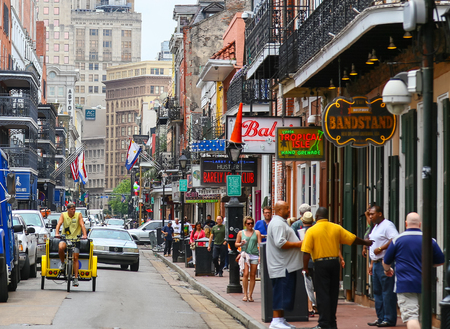 highrises: New Orleans, USA - May 14, 2015: Bourbon Street in French Quarter with many pedestrians and vehicles. There are a lot bars with neon signs, in the back modern highrises.