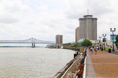highrises: New Orleans, USA - May 14, 2015: New Orleans Riverwalk with the Mississipi River to the left and the Crescent City Connection and highrises in the back. People are strolling down the Riverwalk. Editorial