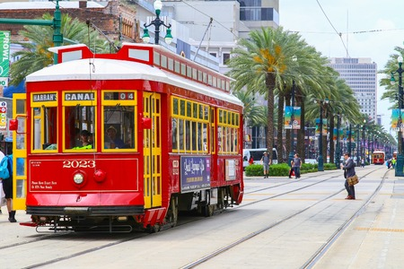 canal street: New Orleans, USA - May 14, 2015: Red streetcar on Canal Street, in the back another streetcar approaching and people crossing the street. Editorial