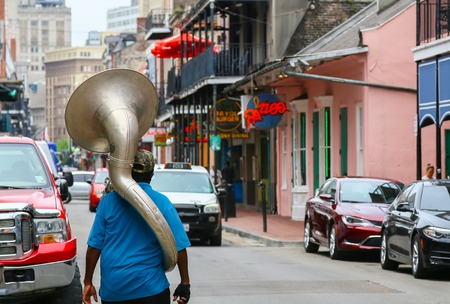 french quarter: New Orleans, USA - May 14, 2015: A man with a sousaphone on his back walking down Bourbon Street in French Quarter. Editorial