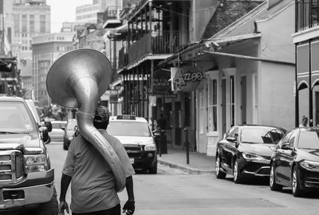 french quarter: New Orleans, USA - May 14, 2015: A man with a sousaphone on his back walking down Bourbon Street in French Quarter. The picture is monochrome.