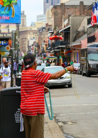 street vendor: New Orleans, USA - May 14, 2015: Street vendor advertising colorful Mardi Gras beads on busy Bourbon Street in French Quarter.