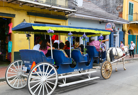 bourbon street: New Orleans, USA - May 14, 2015: Group of people in a carriage on a sightseeing tour on Bourbon Street in French Quarter. Editorial