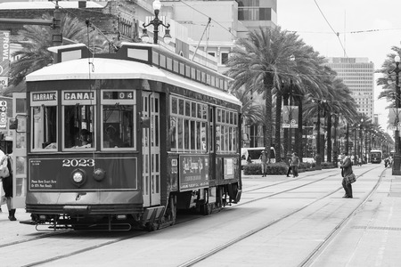 rta: New Orleans, USA - May 14, 2015: Streetcar on Canal Street, in the back another streetcar approaching and people crossing the street. Editorial