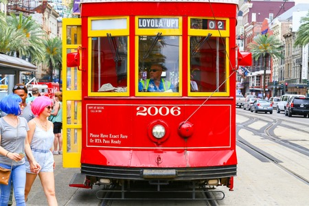 rta: New Orleans, USA - May 14, 2015: Streetcar stopped on Canal Street, two women with colorful wigs crossing the street in front of it.