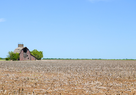 Moundridge, Kansas, USA - May 17, 2015: A derelict barn in the middle of a stubblefield near Moundridge.