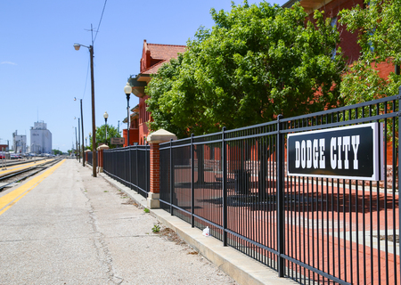great plains: Dodge City, USA - May 17, 2015: Platform of the train station with a retro style sign attached to the fence.