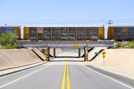 aridness: Gila Bend, USA - May 25, 2015: Union Pacific freight train on a bridge above a road in Gila Bend.