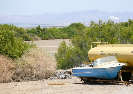 aridness: Calipatria, USA - May 26, 2015: Abandoned boat and water tanker on a parking lot at the Salton Sea.