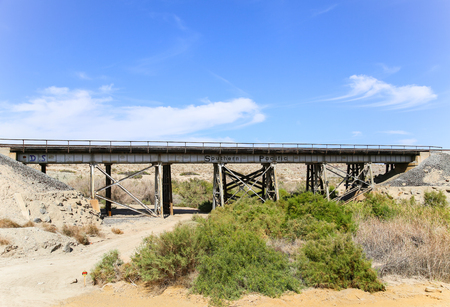 aridness: Durmid, California, USA - May 26, 2015: Rail bridge next to California State Route 111 with the logo of the former railroad company Southern Pacific. Editorial