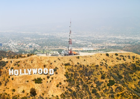 Los Angeles, USA - May 27, 2015: Aerial view of the Hollywood Sign on Mount Lee, on top of the mountain several antennas, in the back Warner Bros. Studios and Forest Lawn Hollywood Hills cemetery.
