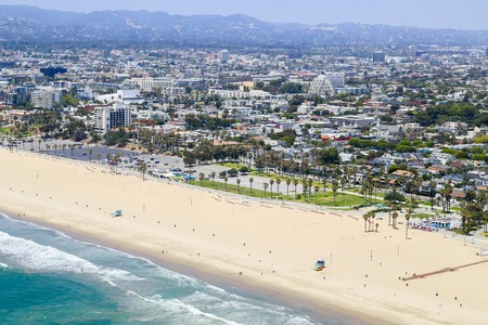 ample: Los Angeles, USA - May 27, 2015: Aerial view of a part of Venice beach with hardly any people on the beach and in the ocean.