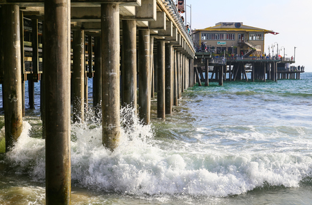 Santa Monica, USA - May 30, 2015: Santa Monica Pier seen from under the pier with waves hitting the planks and the restaurant in the back.