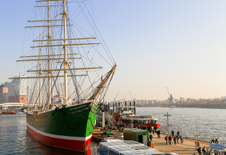 Hamburg, Germany - February 15, 2017 - The three masted barque Rickmer Rickmers moored as a museum ship in the port of Hamburg. People are walking by, in the back a harbor ferry and the concert hall Elbphilharmonie.