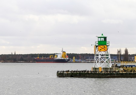 Swinoujscie, Poland - February 21, 2017 - A green Bouy in the harbor. Many cormorants sitting around. In the background a freighter waiting to be loaded.