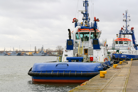 Swinoujscie, Poland - February 21, 2017 - Two tugboats in the harbor are moored at the pier - waiting for use. In the background are several warships.