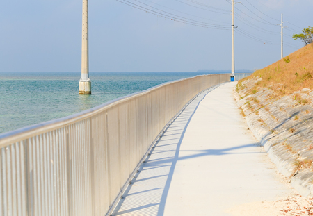 Walkway next to the sea in the Florida Keys with power poles in the water. Archivio Fotografico