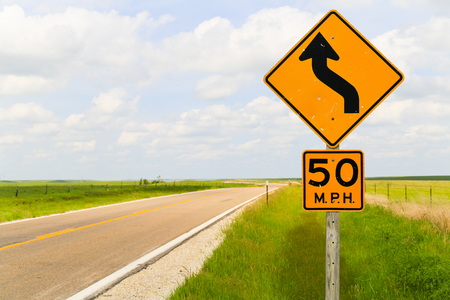 Road signs displaying the maximum speed of 50 mph and that it is a curvy road in the Flint Hills region in Kansas. Stock Photo