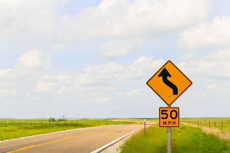 Road sign displaying the maximum speed of 50 mph and that it is a curvy road in the Flint Hills region in Kansas.