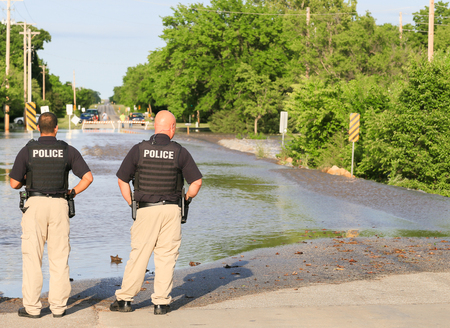 Derby, USA - May 23, 2016: Two policemen cordoning off a flooded street, in the back people with cars in front of the barriers.