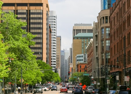 Denver, USA - May 25, 2016: Part of the lower downtown district called LoDo with office buildings and restaurants, cars are driving on the street with roadwork ahead, few people are walking by.