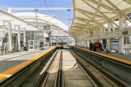 denver buildings: Denver, USA - May 25, 2016: Train on one of the tracks in the open air train hall at the Union Station with people waiting on the platforms. Editorial