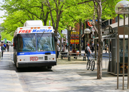 16th street mall: Denver, USA - May 25, 2016: A bus in the 16th street mall in downtown offering free mall ride. People are doing shopping or dining in the several shops and cafes.