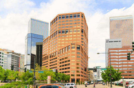 denver buildings: Denver, USA - May 25, 2016: Part of the business and financial district in downtown with several office buildings and green trees, in front pedestrians are hurrying to cross the street.