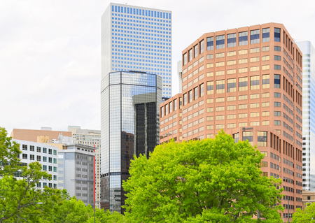 Denver, USA - May 25, 2016: Part of the business and financial district in downtown with several office buildings and green trees in front.