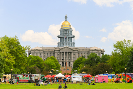 Denver, USA - May 25, 2016: The Colorado State Capitol seen from the Civic Center Park with food trucks in front and people sitting on the lawn.