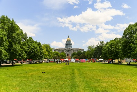 Denver, USA - May 25, 2016: View from the Civic Center Park towards the Colorado State Capitol with food trucks in the back and people sitting on the lawn. Editorial