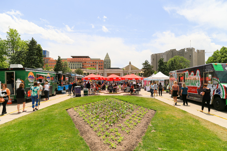 Denver, USA - May 25, 2016: Food truck gathering in the Civic Center park with a busy background of people walking by, standing around or sitting and dining.