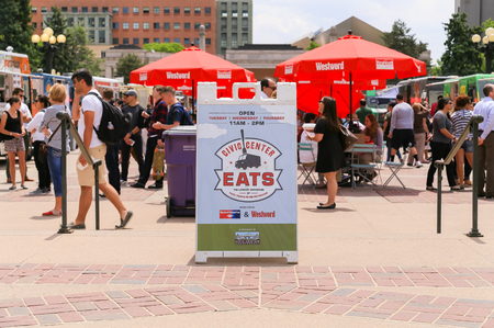Denver, USA - May 25, 2016: Entrance of the food truck gathering in the Civic Center park with a busy background of people walking by, standing around or sitting and dining.