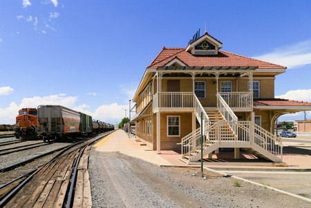 Grand Junction, USA - May 28, 2016: Freight trains on the tracks at the station with the building in front. No passengers are waiting on the platform.