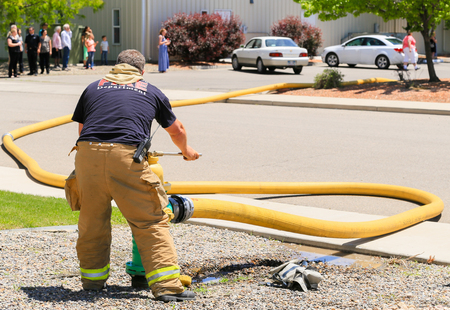 Grand Junction, USA - May 28, 2016: Fireman in action connecting a fire hose to a hydrant. In the back bystanders are watching the scene.