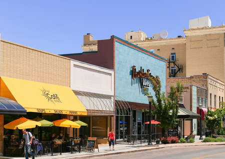 Grand Junction, USA - May 28, 2016: Cafe with outside dining and shops on the main street of the city. People are walking by.