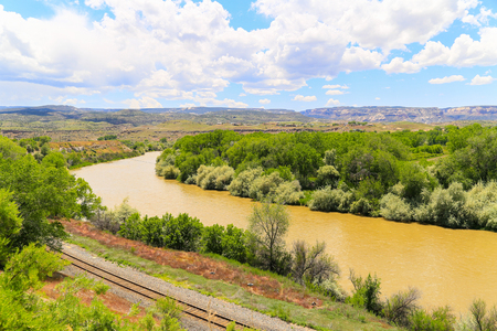 Railroad tracks next to the Gunnison River near Grand Junction in Colorado with the Book Cliffs in the back.