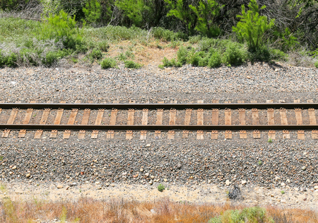 Straight railroad tracks in a gravel bed with vegetation to both sides. Stock Photo