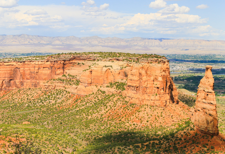 The rock formation Independence Monument and Monument Canyon as part of the Colorado National Monument. In the back the Book Cliffs.