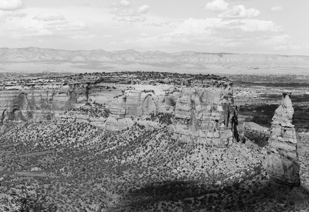 The rock formation Independence Monument and Monument Canyon as part of the Colorado National Monument. In the back the Book Cliffs. The picture is in monochrome. Stock Photo