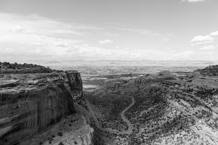 Cars driving on the Rim Rock Drive in the Fruita Canyon as part of the Colorado National Monument with the Book Cliffs in the back. The picture is in monochrome.