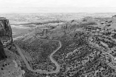 The Rim Rock Drive, the road going through the Colorado National Monument, winding through the  Fruita Canyon. In the back the Book Cliffs. The picture is in monochrome.